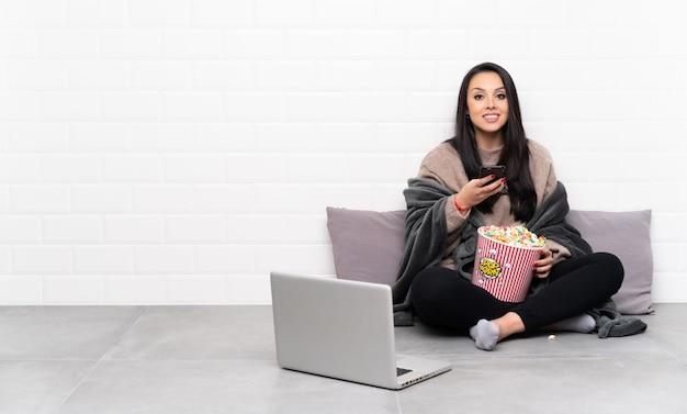 ポップコーンのボウルを保持していると携帯電話でメッセージを送信するラップトップで映画を見せてコロンビアの若い女性
