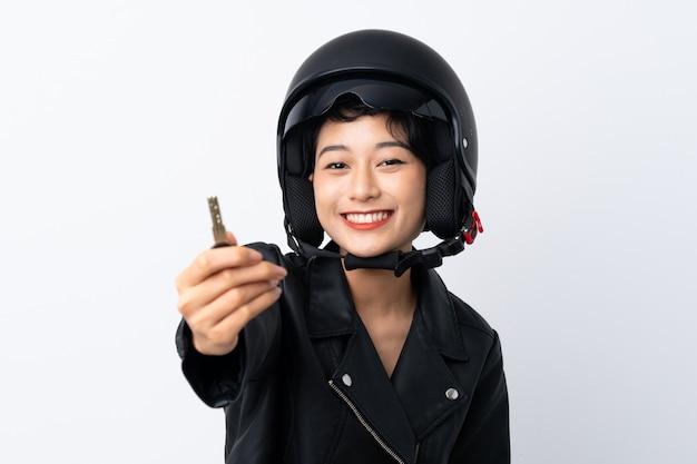 オートバイのヘルメットと孤立した白い壁の上のキーを持つ若いアジアの女の子