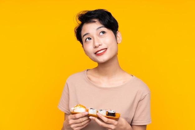寿司を見ながら笑顔でアジアの少女