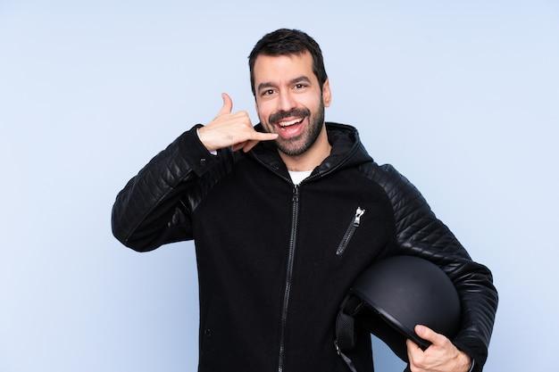 電話のジェスチャーを作る孤立した壁の上のオートバイのヘルメットを持つ男。電話して、手話
