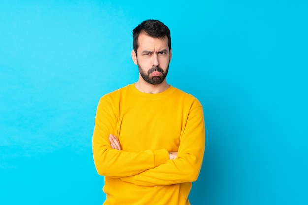 Молодой кавказский человек над изолированной голубой стеной чувствуя расстроенный
