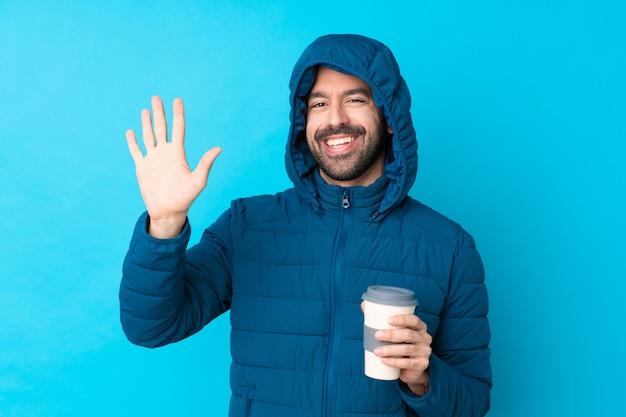 冬のジャケットを着て、幸せな表情で手で敬礼分離の青い壁に持ち帰り用のコーヒーを保持している男