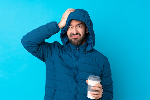 Укомплектуйте личным составом нося зимнюю куртку и держащ кофе на вынос над изолированной голубой стеной с выражением разочарования и не понимания