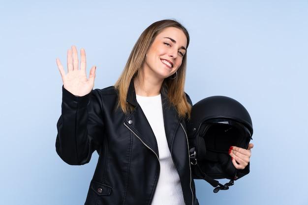 幸せな表情で手で敬礼分離の青い壁の上のオートバイのヘルメットを持つ若いブロンドの女性