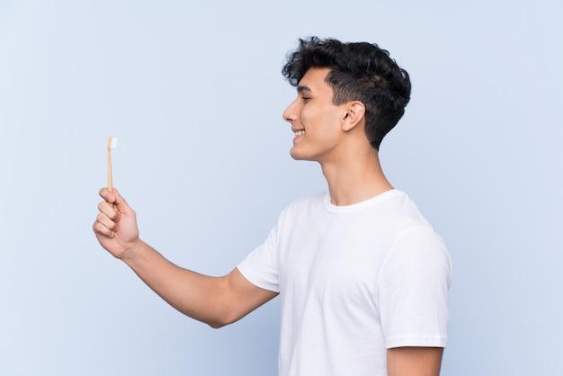 Молодой аргентинский человек чистит зубы над синей стеной с счастливым выражением