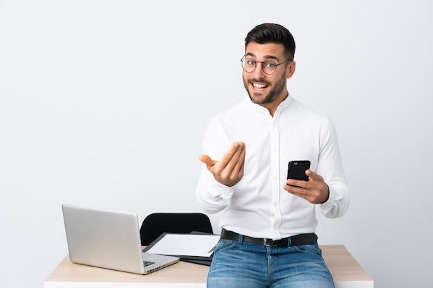Молодой предприниматель держит мобильный телефон, приглашая прийти
