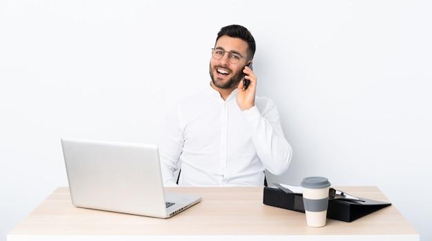 Молодой предприниматель на рабочем месте, ведение разговора с мобильным телефоном
