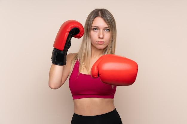 Молодая спортивная блондинка над изолированной стеной с боксерскими перчатками