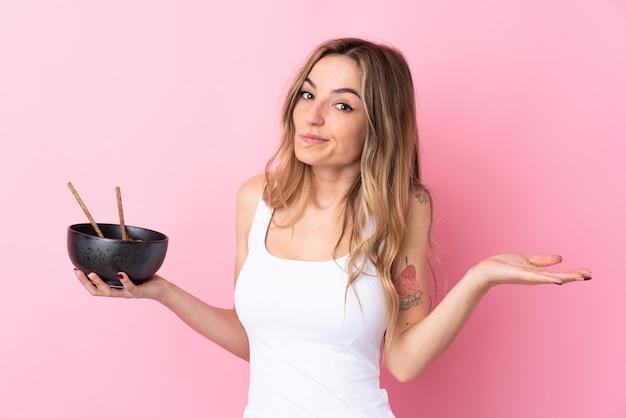 箸で麺のボウルを押しながら肩を持ち上げながら疑問ジェスチャーを作る分離のピンクの壁の上の若い女性