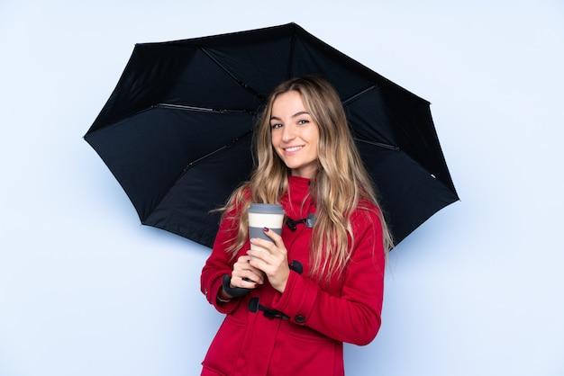 Молодая женщина с зимним пальто держит зонтик и кофе на вынос