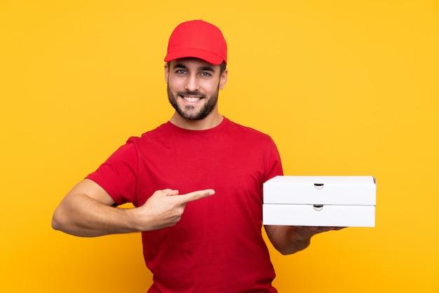 孤立した黄色の壁の上のピザの箱を拾って、それを指している作業服のピザ配達人