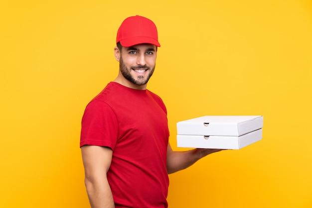 Работник службы доставки пиццы с рабочей формой подбирает коробки для пиццы на изолированной желтой стене и много улыбается