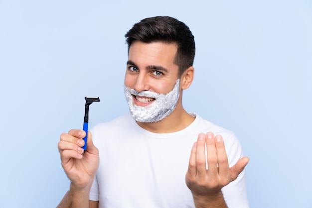 若いハンサムな男が手に来るように招待して孤立した壁に彼のひげを剃る。あなたが来て幸せ