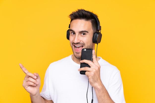Молодой человек над желтой стеной прослушивания музыки с мобильного телефона и пения