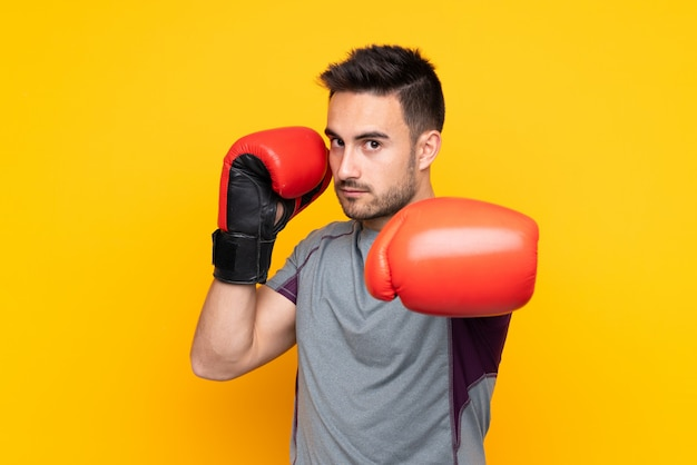 ボクシンググローブで孤立した黄色の壁の上のスポーツ男