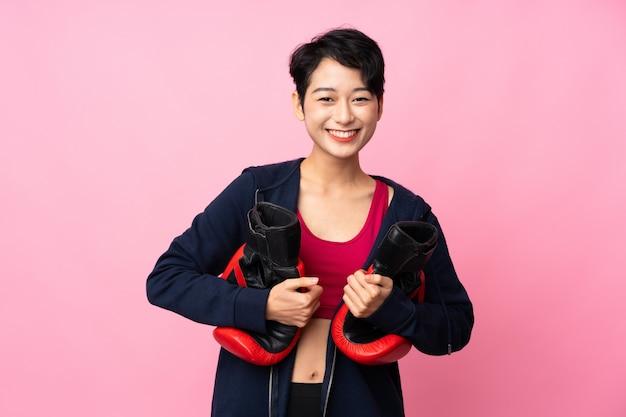 ボクシンググローブで孤立したピンクの壁を越えて若いスポーツアジアの女性