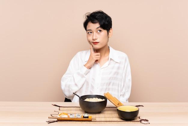 麺と寿司のアイデアを考えてのボウルとテーブルの若いアジア女性