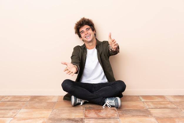 提示し、手に来ることを誘って床に座っている若い白人男