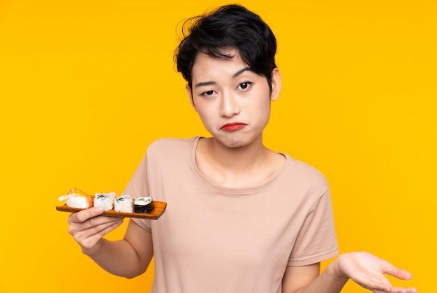 肩を持ち上げながら疑いジェスチャーを作る寿司を持つ若いアジア女性