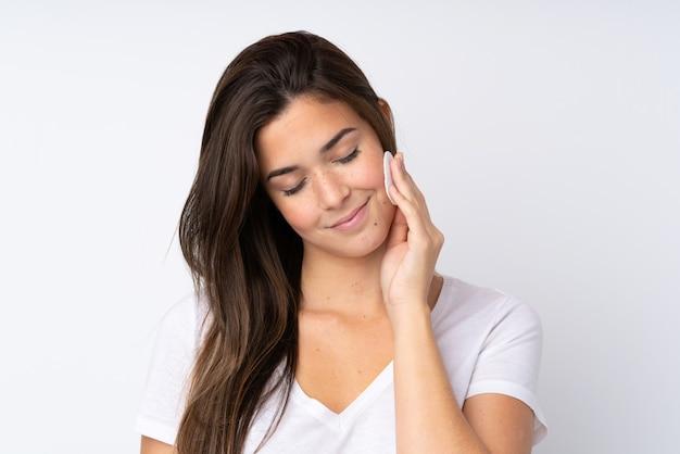 Женщина подросток над изолированной стеной с ватным тампоном для снятия макияжа с ее лица