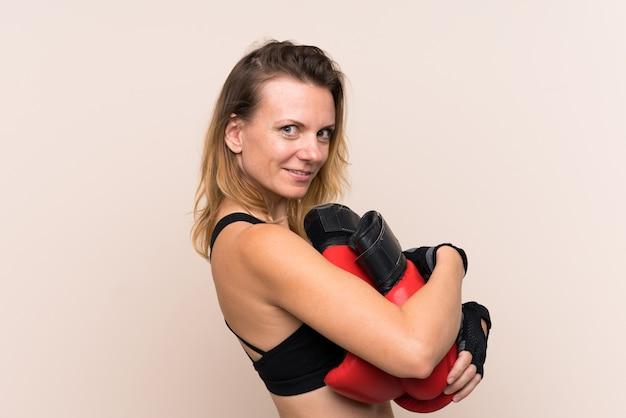 ボクシンググローブで孤立した壁を越えて金髪スポーツ女性