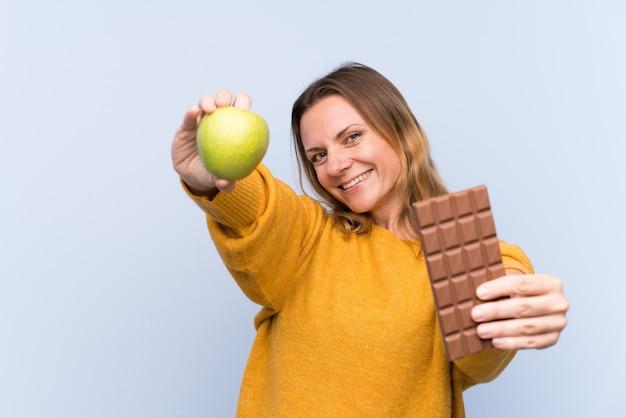 片方の手でチョコレートタブレットと他の手でリンゴを取って孤立した青い壁の上の金髪の女性
