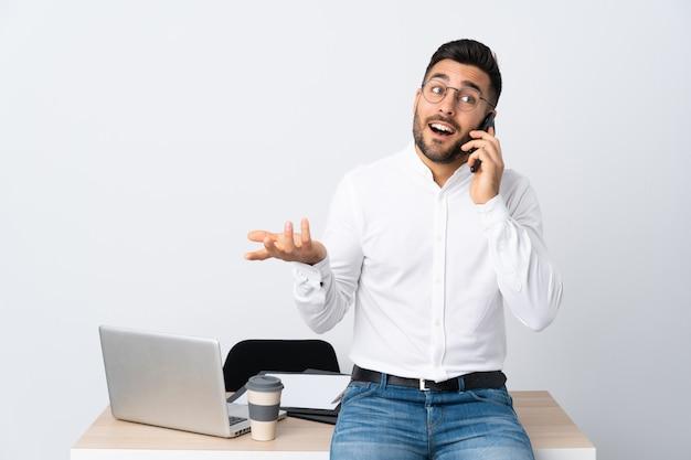 Молодой предприниматель держит мобильный телефон