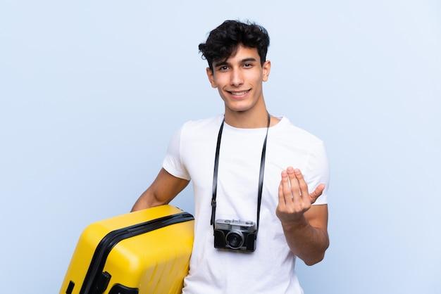 手で来ることを誘って分離の青い壁の上の若いアルゼンチン旅行者の男。あなたが来て幸せ