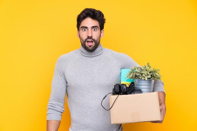 驚きとショックを受けた表情で孤立した壁の上の物でいっぱいの箱を拾いながら動きを作るひげの若いハンサムな男