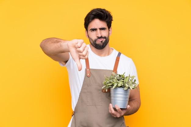 サインダウン親指を示す分離の黄色の壁の上のひげを持つ庭師男