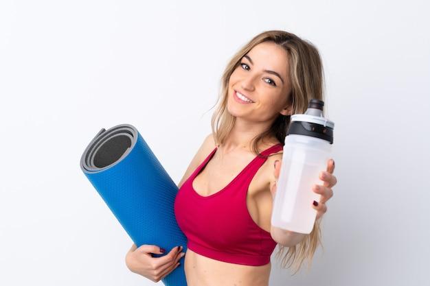 スポーツ水筒とマットの分離の白い壁の上の若いスポーツ女性