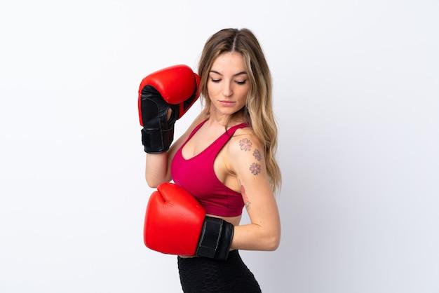 ボクシンググローブで孤立した白い壁の上の若いスポーツ女性