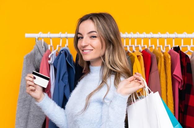 クレジットカードと買い物袋を保持している衣料品店の若い女性