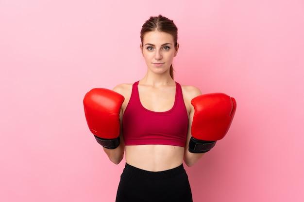 ボクシンググローブで孤立したピンクの壁の上の若いスポーツ女性