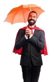 傘を持っているスーパーヒーローのビジネスマン