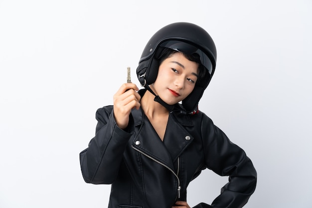 Молодая азиатская девушка с мотоциклетным шлемом и ключом над изолированной белой стеной