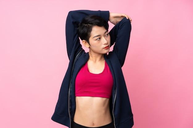 若いスポーツアジア女性の孤立したピンクの壁のストレッチ
