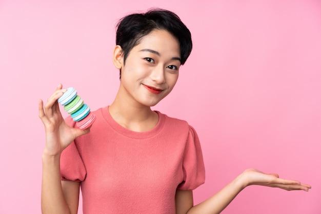 カラフルなフランスのマカロンを押し、ジェスチャーを疑って分離のピンクの壁の上の若いアジアの女の子