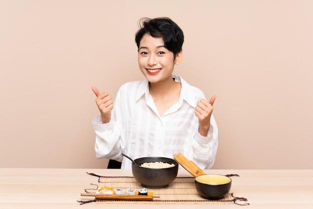 麺と寿司のジェスチャーを親指を与えるボウルとテーブルの若いアジアの女の子