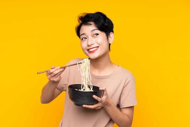 箸で麺のボウルを押しながら見上げる孤立した黄色の壁の上の若いアジアの女の子