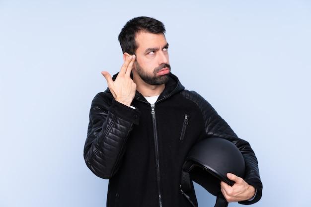 自殺ジェスチャーを作る問題と孤立した壁の上のオートバイのヘルメットを持つ男