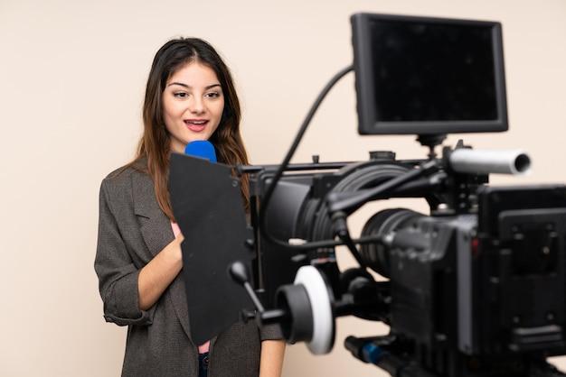 Женщина репортера держа микрофон и сообщая новости над изолированной белой стеной