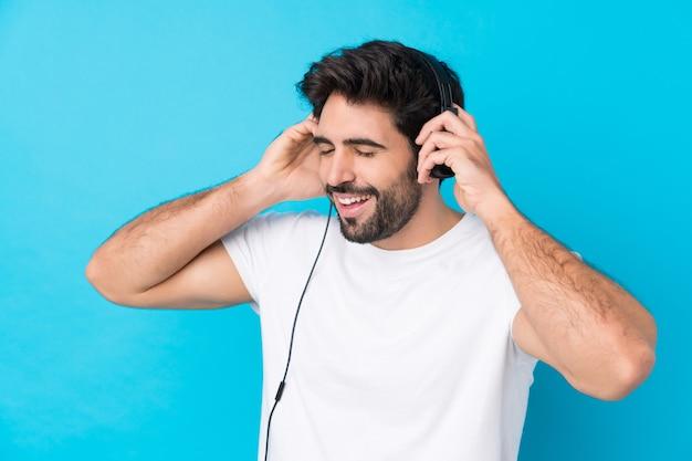 Молодой красивый человек с бородой над изолированной синей стеной прослушивания музыки и пения