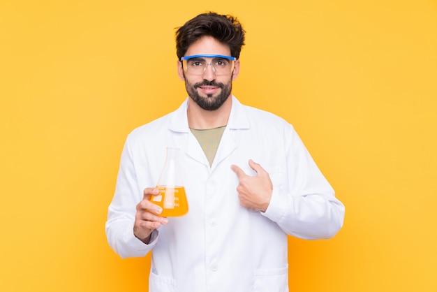 Молодой ученый над изолированной желтой стеной с удивленным выражением лица