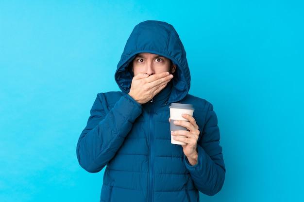 Укомплектуйте личным составом носить зимнюю куртку и держа кофе на вынос по изолированному голубому рту покрытия стены руками