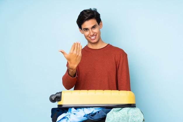 Человек с чемоданом, полным одежды над синей стеной, приглашая прийти