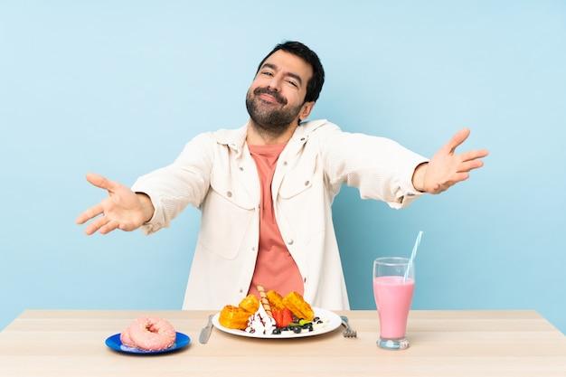 朝食ワッフルとミルクシェークを提示し、手に来るように招待してテーブルで男