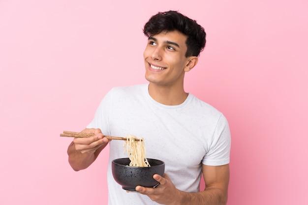 箸で麺のボウルを保持していると見上げる若いアルゼンチン人