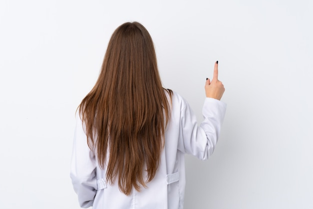 Молодая женщина над изолированной стеной носить платье доктора и указывая назад