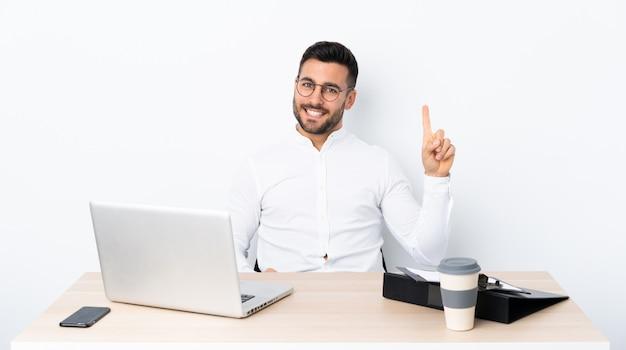 表示し、最高の兆候で指を持ち上げる職場の青年実業家